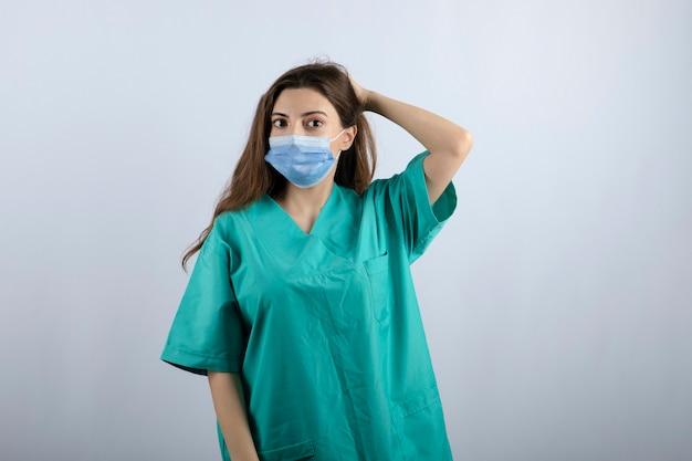 Jeune belle infirmière en uniforme vert portant un masque médical