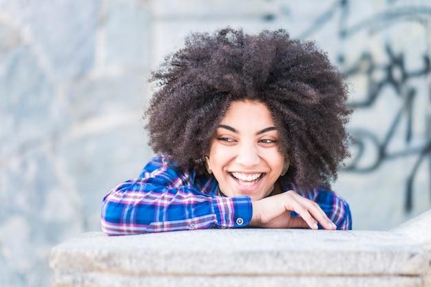 Jeune belle jeune femme aux cheveux africains riant et s'amusant dans une ville en plein air