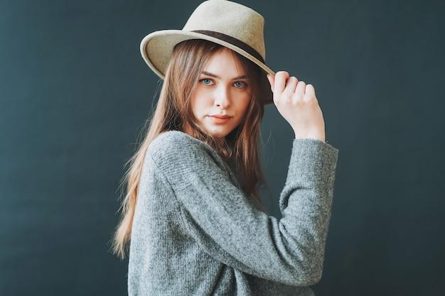Jeune belle jeune fille aux cheveux bruns en chapeau de feutre et pull en tricot gris regardant la caméra sur fond sombre