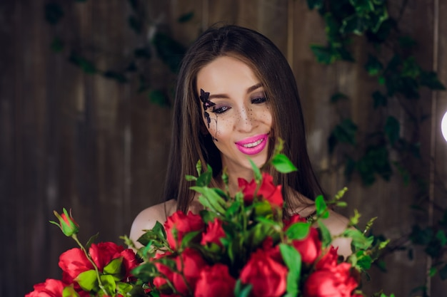 Jeune belle jolie fille debout et tenant la boîte avec des roses rouges. vogue fashion style studio portrait fille en robe élégante noire debout