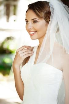Jeune belle mariée blonde en robe de mariée et voile souriant.