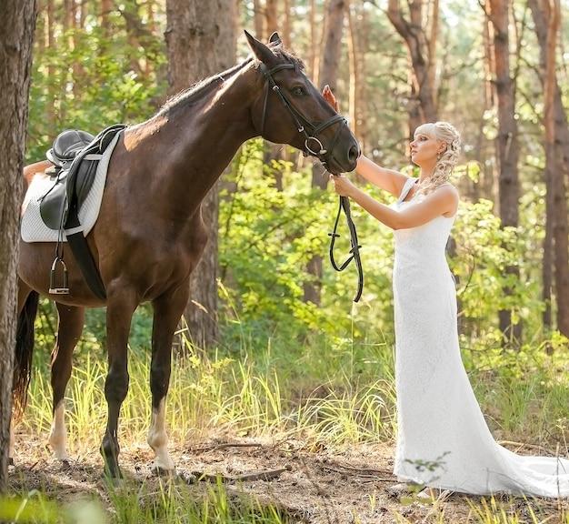 Jeune belle mariée et cheval sur la nature