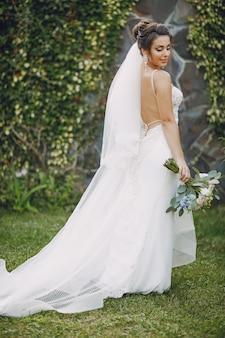 Une jeune et belle mariée est debout dans un parc d'été avec bouquet de fleurs