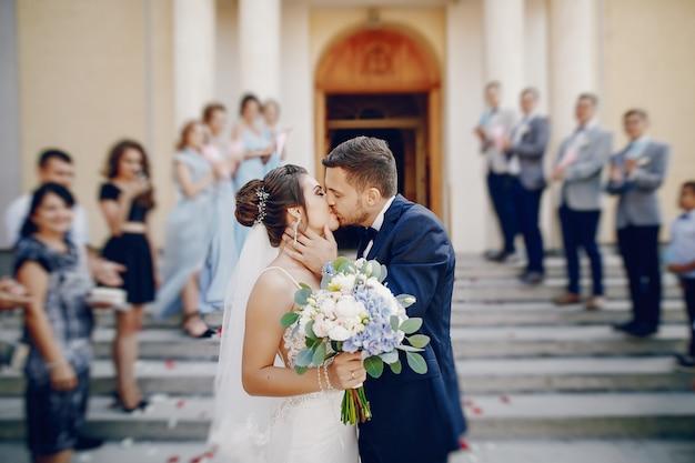 Une jeune et belle mariée est debout près de la maison avec son mari