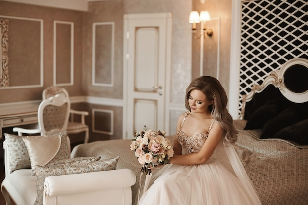 Jeune et belle mariée heureuse blonde modèle fille avec un maquillage doux et avec une coiffure de mariage en t...