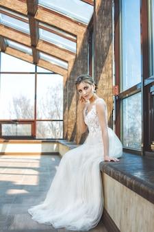 Jeune belle mariée heureuse luxueuse dans une robe de mariée à la mode dans le hall avec de grandes fenêtres
