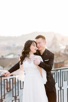 Jeune belle mariée et le marié asiatique, couple heureux au coucher du soleil dans la vieille ville européenne.