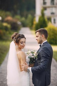 Une jeune et belle mariée et son mari debout dans le parc avec bouquet de fleurs