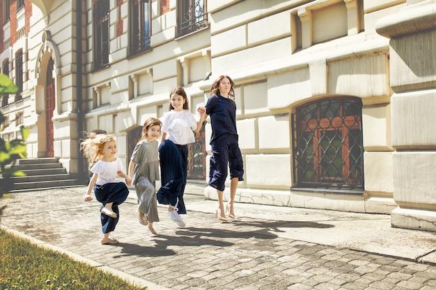 Jeune belle mère adulte et sa petite gaie et ses filles marchent ensemble dans les rues de la ville