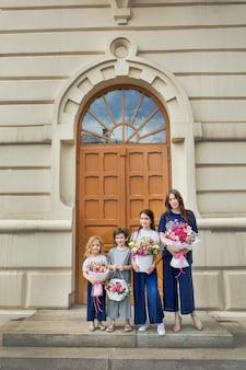Jeune belle mère adulte et ses petites filles gaies et heureuses avec des bouquets de fleurs