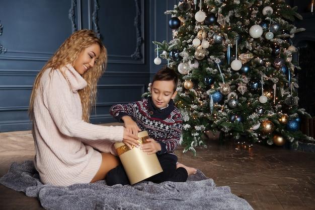 Jeune belle mère asiatique avec son petit fils assis près d'un arbre de noël décoré et échange des cadeaux.