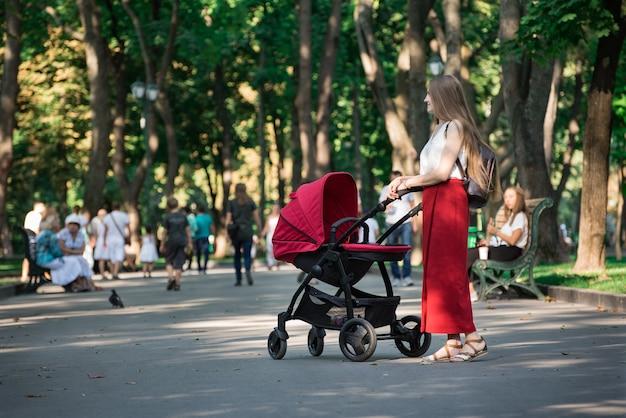 Jeune belle mère dans le parc d'été avec un landau. concept de maternité heureuse