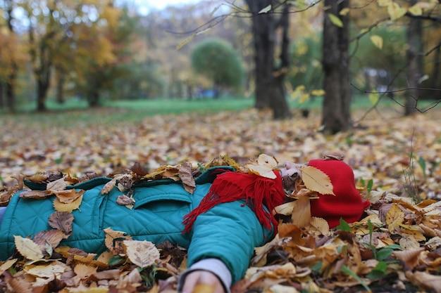Jeune belle mère avec sa fille sur la nature. une fille au chapeau se promène dans le parc. fille dans le parc de la ville d'automne à la chute des feuilles.