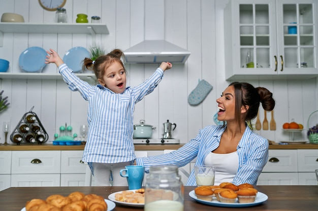 Jeune belle mère et sa petite fille jouant dans la cuisine pendant le petit déjeuner à la maison.