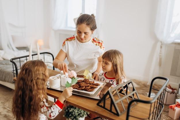 Jeune belle mère et ses deux charmantes petites filles s'assoient à table et vont boire du cacao avec des guimauves et des biscuits dans la salle cosy avec le sapin du nouvel an .