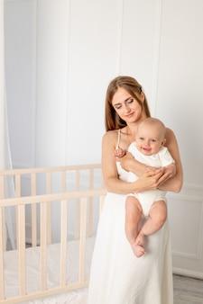 Jeune belle mère tenant sa fille 6 mois dans la crèche, fête des mères, place pour le texte.