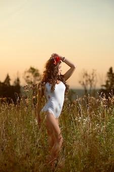 Jeune, belle, modèle attrayant en maillot de bain, posant dans un champ de fleurs