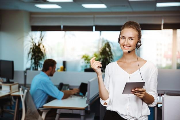 Jeune belle opérateur téléphonique de soutien féminin parlant, consultant, sur le bureau