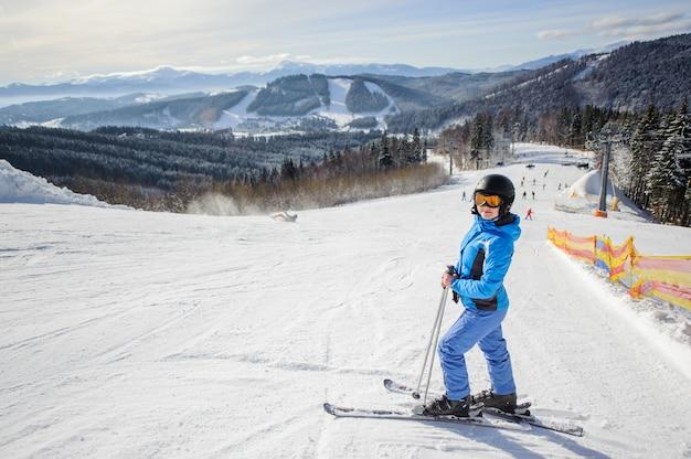 Jeune belle skieuse au milieu d'une piste de ski