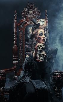 Jeune belle sorcière est assise sur une chaise. maquillage lumineux, crâne, thème fumée-halloween.