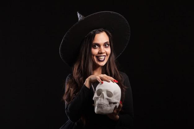 Jeune belle sorcière en robe noire faisant de la sorcellerie sur un crâne humain. sorcière mystérieuse dans une robe noire pour halloween.