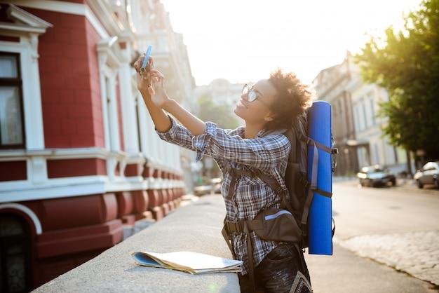 Jeune belle voyageuse africaine avec sac à dos souriant, faisant selfie.