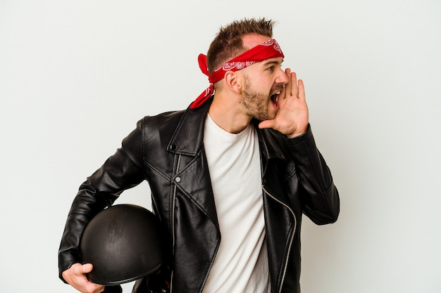 Jeune biker tatoué homme caucasien tenant un casque isolé sur fond blanc criant et tenant la paume près de la bouche ouverte.
