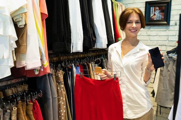 Jeune, blanc, femme, tient, jupe rouge, et, téléphone portable, dans, elle, mains