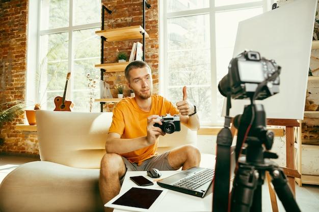 Jeune blogueur caucasien avec équipement professionnel enregistrement vidéo examen de la caméra à la maison. blog, vidéoblog, vlog. homme faisant un vlog ou un flux en direct sur une photo ou une nouveauté technique.