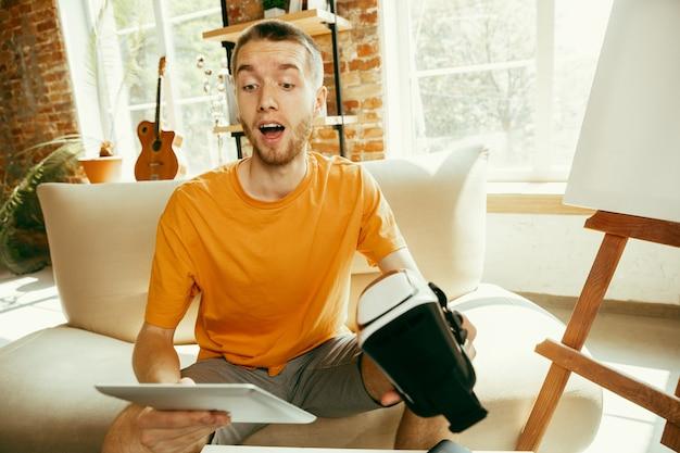 Jeune blogueur caucasien avec équipement professionnel enregistrement vidéo examen de lunettes vr à la maison. blog, vidéoblog, vlog. homme faisant un vlog ou un flux en direct sur une photo ou une nouveauté technique.