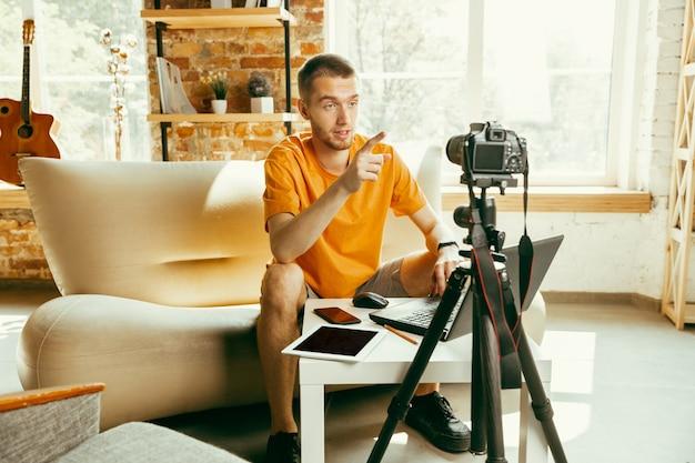 Jeune blogueur caucasien avec examen vidéo d'enregistrement de caméra professionnelle de gadgets à la maison. blog, vidéoblog, vlog. homme faisant un vlog ou un flux en direct sur la photo ou la nouveauté technique.
