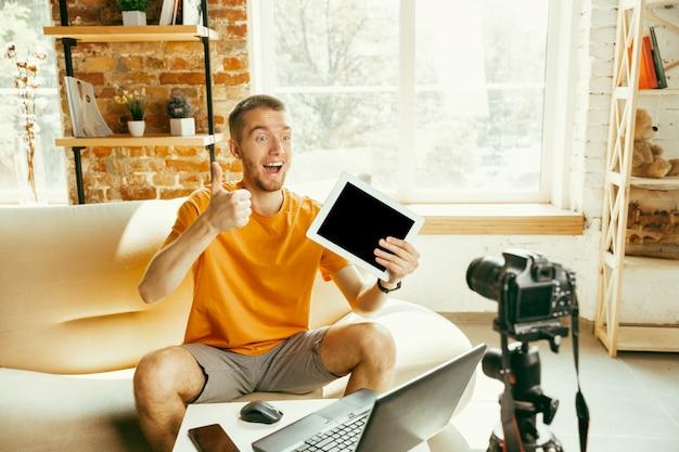 Jeune blogueur caucasien avec examen vidéo d'enregistrement de caméra professionnelle de la tablette à la maison. blog, vidéoblog, vlog. homme faisant un vlog ou un flux en direct sur une photo ou une nouveauté technique.