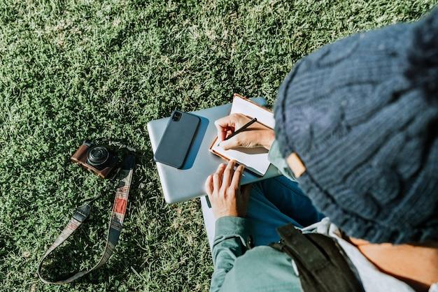Un jeune blogueur écrit dans son bloc-notes aime la vie de nomade numérique. concept: travail à distance