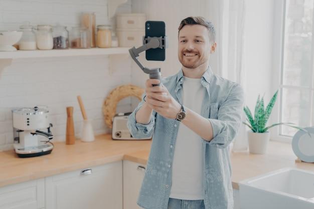 Un jeune blogueur enregistre un blog vidéo ou une diffusion en direct avec un smartphone et un cardan à l'intérieur, debout sur fond de cuisine. vlog de tournage de vlogger de médias sociaux, podcast en ligne en streaming sur téléphone mobile