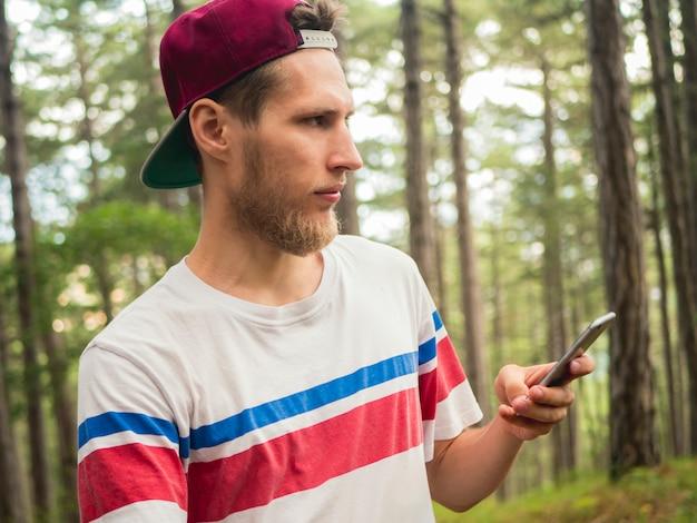 Jeune blogueur hipster barbu faire flux en direct dans les réseaux sociaux à pied dans la forêt