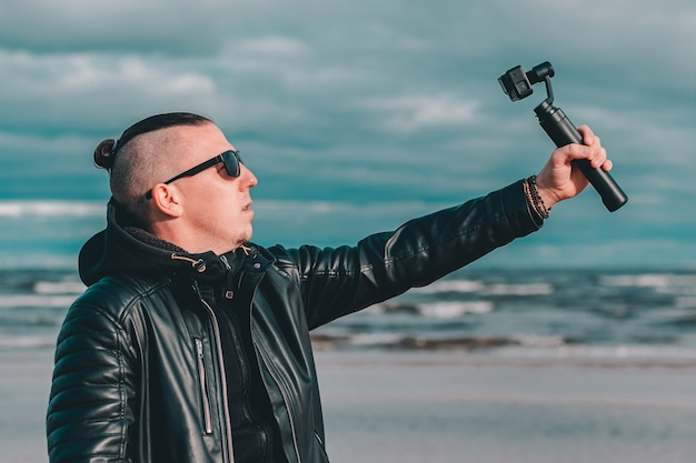 Jeune blogueur en lunettes de soleil faisant selfie ou vidéo en streaming à la plage à l'aide d'une caméra d'action avec stabilisateur de caméra à cardan.
