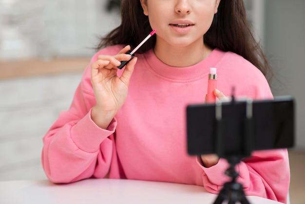 Jeune blogueur mettant du brillant à lèvres