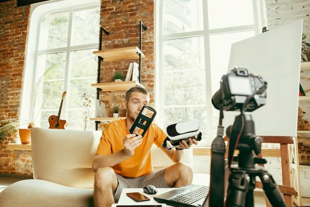 Jeune blogueur de race blanche avec un équipement professionnel enregistrement vidéo examen de lunettes vr à la maison