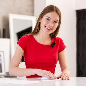 Jeune blogueur souriant et pliant un papier