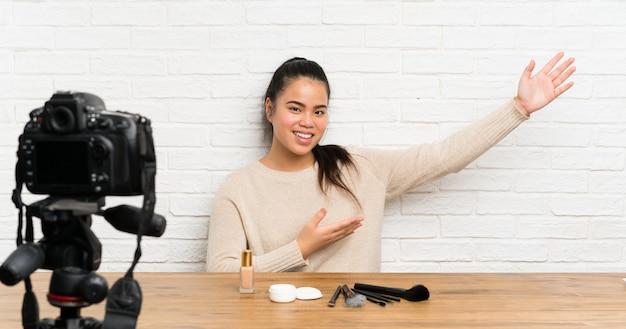 Une jeune blogueuse asiatique qui enregistre un didacticiel vidéo qui étend les mains sur le côté pour l'inviter à venir