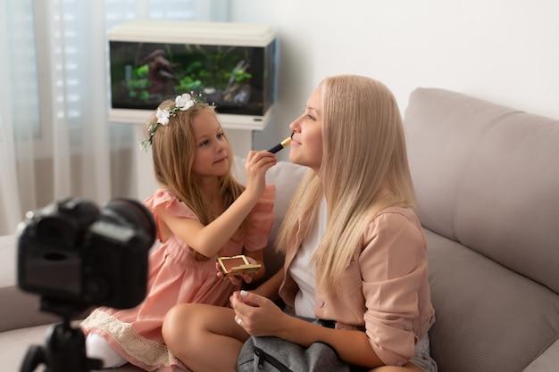 Jeune blogueuse beauté et sa douce fille enregistrant une vidéo à la maison