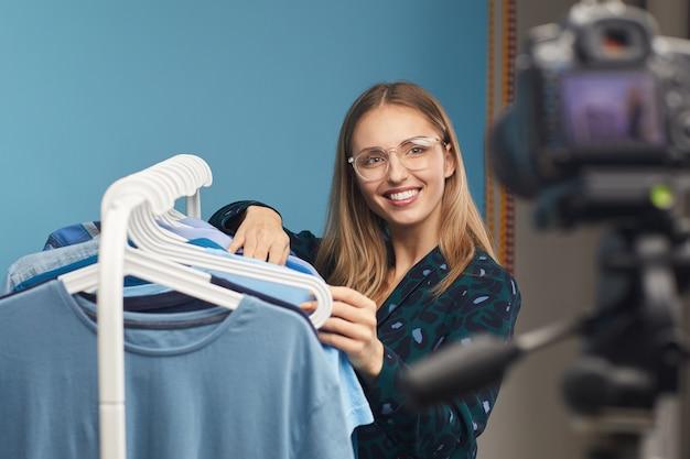 Jeune blogueuse beauté souriant à la caméra tout en se tenant près du rack avec des vêtements et en filmant la vidéo pour son contenu
