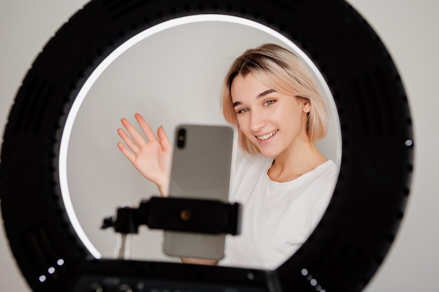 Une jeune blogueuse diffuse en direct en ligne à la maison avec une lampe annulaire et un smartphone