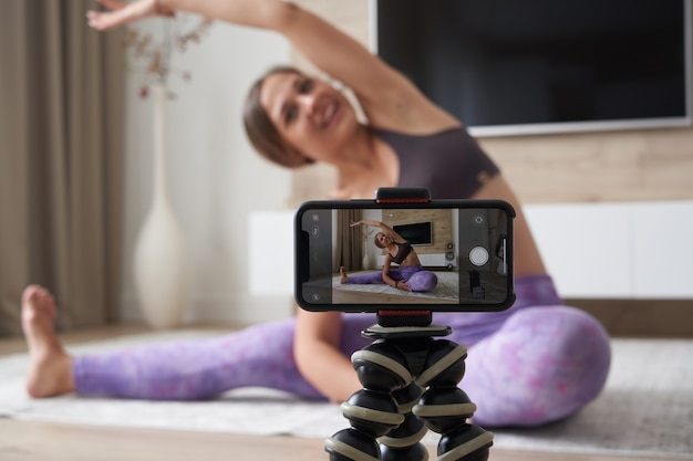 Jeune blogueuse enregistrant une vidéo sportive à la maison faisant du yoga dans le salon