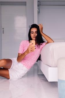 Jeune blogueuse de mode femme assez caucasienne portant des vêtements élégants, prenant selfie photo