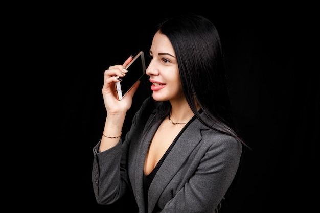 Jeune blogueuse de mode joyeuse et prospère parlant au téléphone, appréciant la conversation. petite amie détendue insouciante dans un smartphone décontracté plus doux.