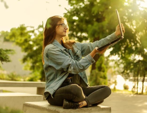 Une jeune blogueuse moderne dans une veste en jean et des lunettes tient un ordinateur portable dans ses mains dans le parc. apprentissage en ligne, blogs