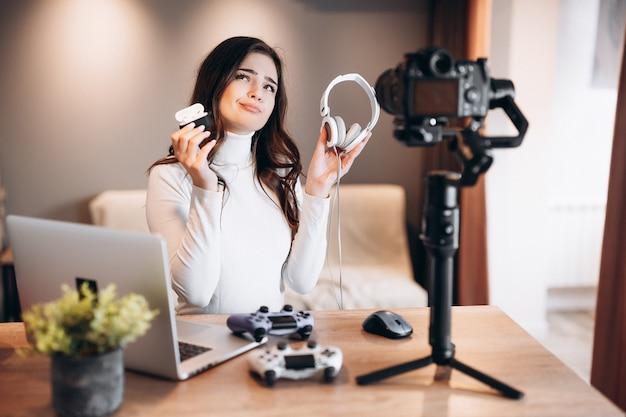 Une jeune blogueuse avec un ordinateur portable et des manettes filme et montre sa préférence dans les écouteurs pour les jeux vidéo. influenceuse jeune femme en direct en streaming.