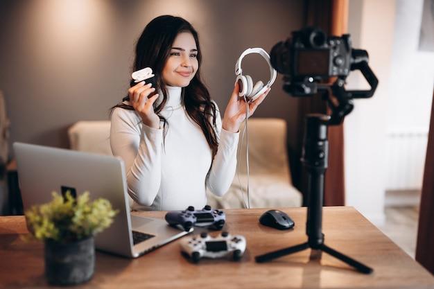 Une jeune blogueuse avec un ordinateur portable et des manettes filme et montre sa préférence dans les écouteurs pour les jeux vidéo. influenceuse jeune femme en streaming en direct à la maison.