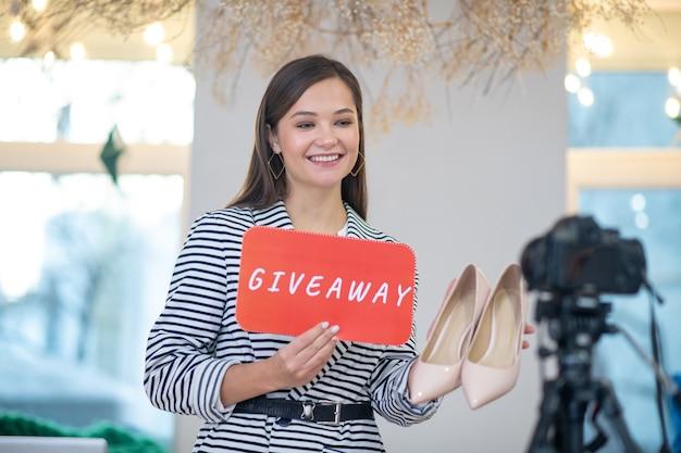 Jeune blogueuse positive souriant tout en faisant la promotion de son cadeau pour des chaussures
